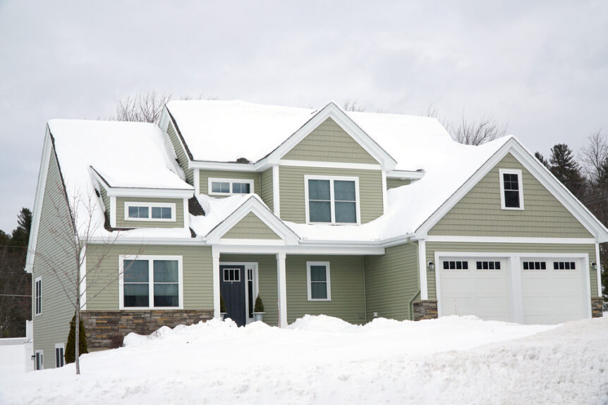 vacant home in winter covered in snow