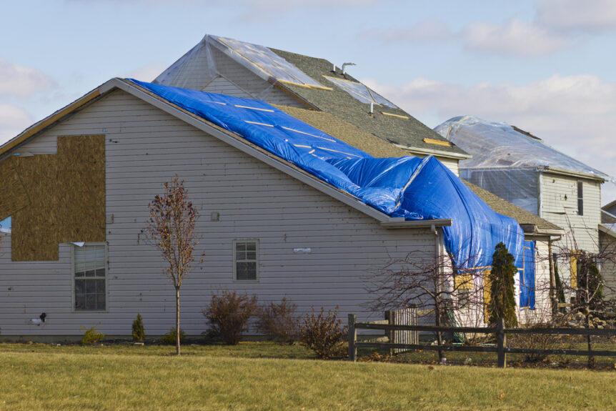home damaged by storm with blue tarp over roof and siding missing