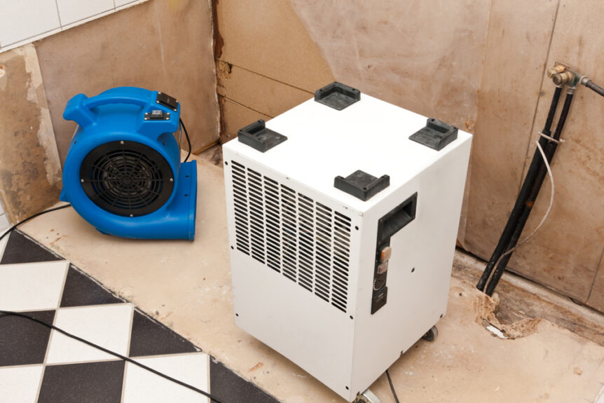 professional water damage restoration air mover and dehumidifier drying out room damaged by water