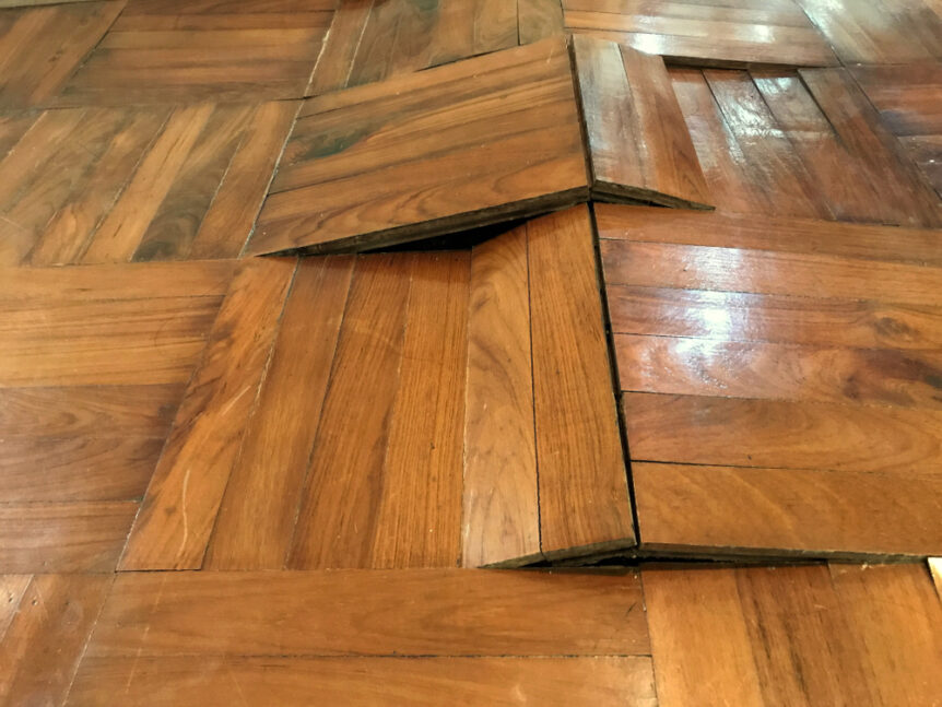 older wood floors that have buckled due to water damage and moisture inside house